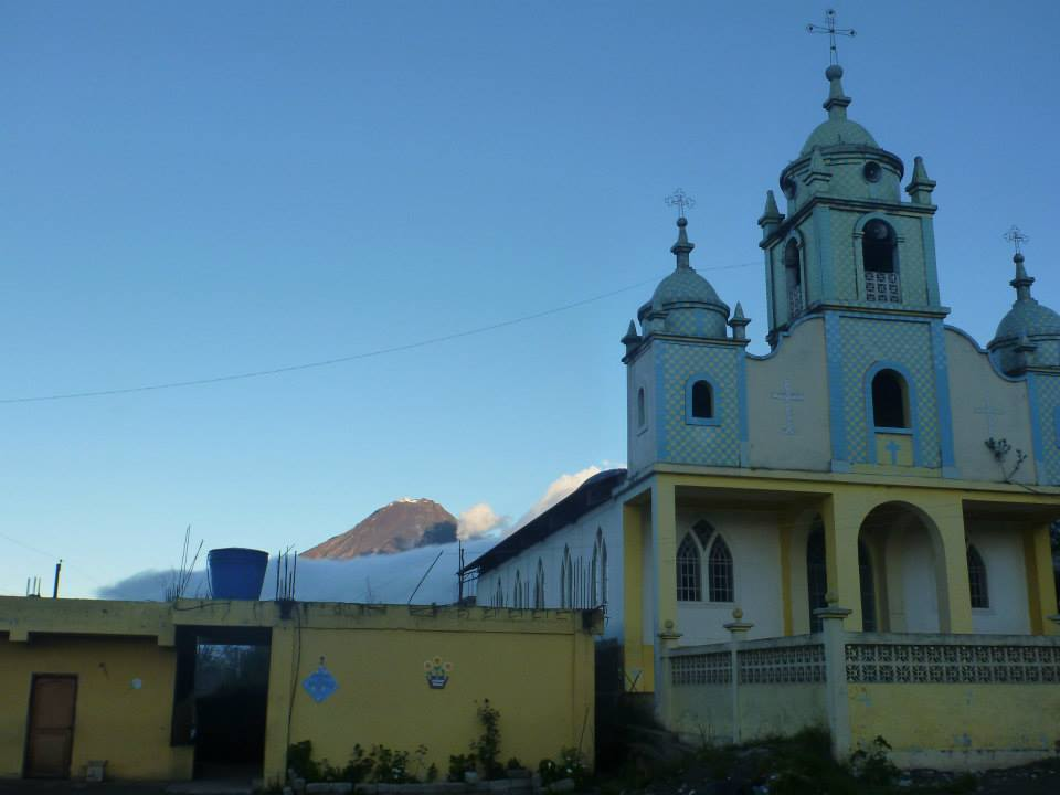 Tungurahua, in the evening light, pokes our from behind a church in the nearby town of Pelileo.